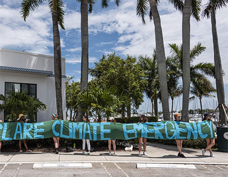 Samantha Gazda with other activists outside Miami City Hall with a banner that reads: declare climate emergency